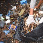 imagen de mano depositando basura en bolsa #BasuraChallengeAcajutla
