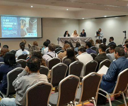 fotografía del evento presentación del informe sobre desplazamientos forzados internos, en la imagen se muestra la proyección de la caratula del informe, la mesa de presentadores del informe y la audiencia.